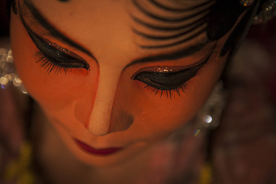 A detail shot of a Chinese opera performer just before she goes on stage. Chinese opera is performed in Thailand by itinerant groups of players, most of whom are from the northeastern region of Thailand known as Isan. It is characterised by its lavish costumes, the falsetto delivery of its actors and the highly stylised presentation of its set-piece stories which are drawn from Chinese folklore. Though the operas are performed in Chinese most of the actors don't understand Chinese and simply learn their parts by rote. Chinese opera is colourful reminder of the importance of Thailand's ethnic Chinese population, and of how Chinese culture has become an integral part of Thailand's cultural identity. Though the Chinese opera is appreciated by an ageing, and dwindling, population of Chinese speakers, the performers explain that audience sizes is of little importance since they essentially performing for the gods. The shows are usually sponsored by the local community, are free for all to attend and usually last between two and three days.